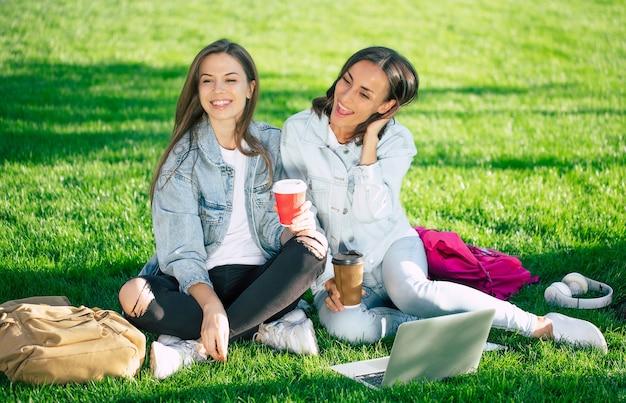 Deux amies heureux et belle jeune étudiante en denim décontracté se détendent dans le parc universitaire avec ordinateur portable et smartphone par l'université et buvant du café.