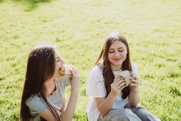 Deux amies de jeunes femmes mangeant de délicieux hamburgers dans le parc sur l'herbe. pas une alimentation saine. mise au point sélective douce, défocalisation.
