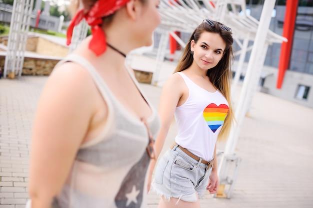 Deux amies lesbiennes embrassent et sourient à l'extérieur.