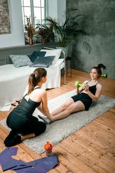 Deux amies à la maison bavardent, sourient et font du sport
