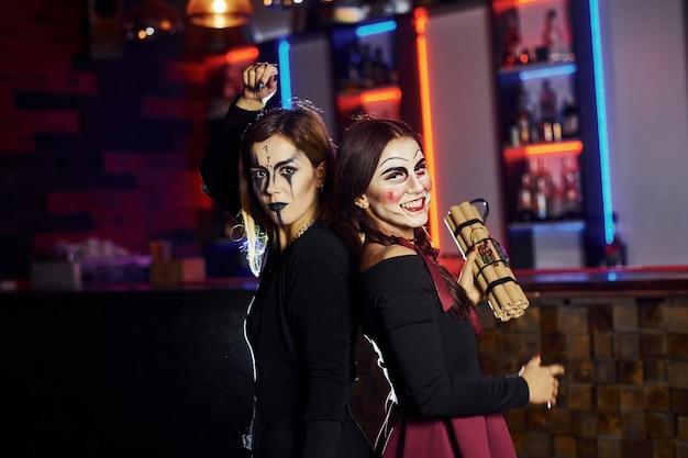 Deux amies participent à la soirée thématique d'halloween en maquillage effrayant et costumes avec bombe à retardement.