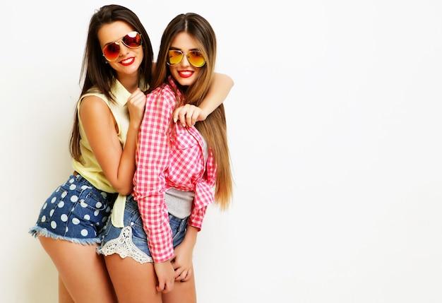 Deux amies peintes riant de la mode s'embrassant et s'amusant