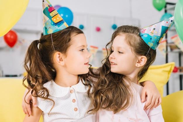 Deux amies portant un chapeau de fête se regardant
