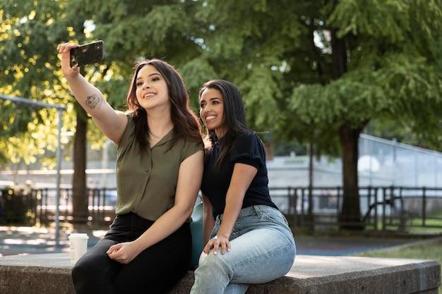 Deux amies prenant un selfie dans le parc tout en buvant un café
