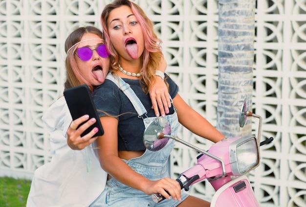 Deux amies prenant un selfie sur scooter