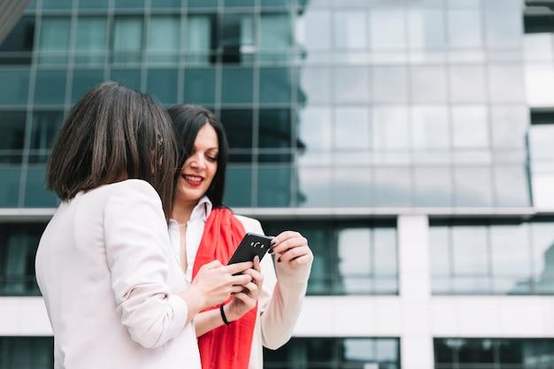Deux amies en regardant un téléphone mobile avec la construction en arrière-plan