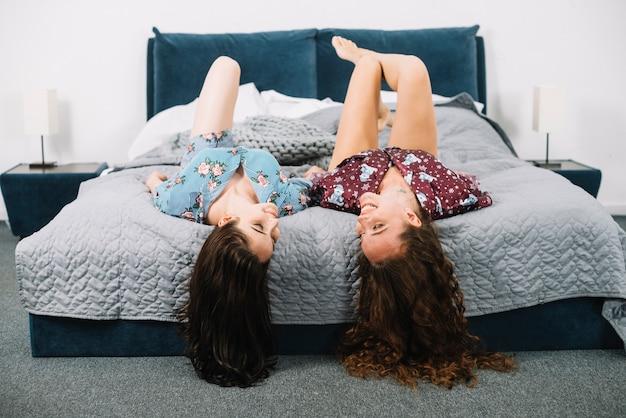 Deux amies reposantes sur le lit à la maison