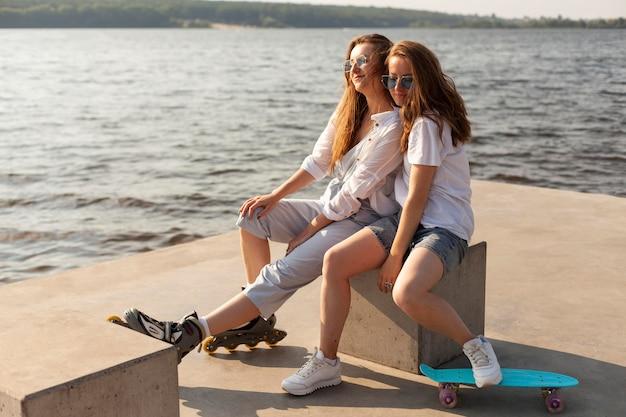 Deux amies s'amusant au bord du lac avec des patins à roulettes