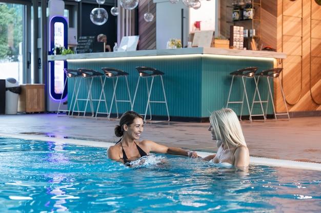 Deux amies s'amusant ensemble dans la piscine groupe de femmes souriantes dans une piscine