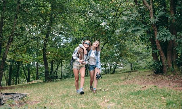 Deux amies avec des sacs à dos embrassées et riant en marchant dans la forêt