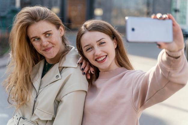 Deux amies smiley à l'extérieur dans la ville en prenant un selfie
