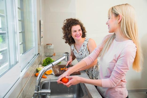 Deux amies souriantes travaillant dans la cuisine se regardant
