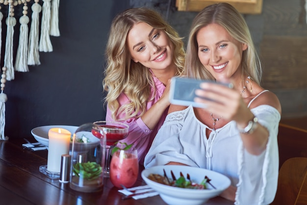 Deux amies en train de déjeuner au restaurant et à l'aide de smartphone