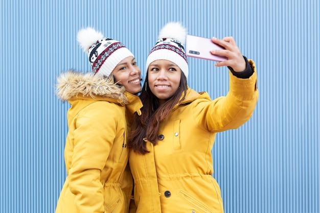 Deux amies vêtues du même ensemble de vêtements d'hiver prenant une photo d'elles-mêmes avec un téléphone intelligent