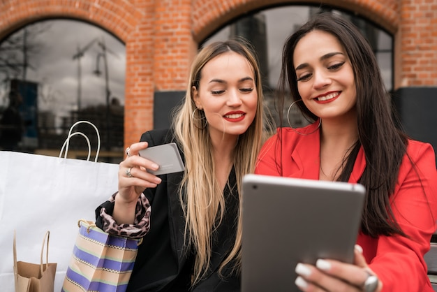 Deux amis, achats en ligne avec carte de crédit et tablette numérique.