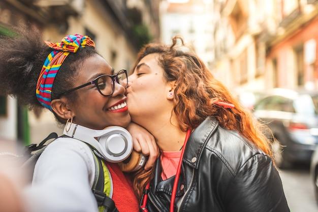 Deux amis adolescents prenant un selfie à l'extérieur.