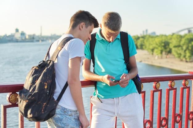 Deux amis adolescents utilisant un smartphone, parlant et souriant