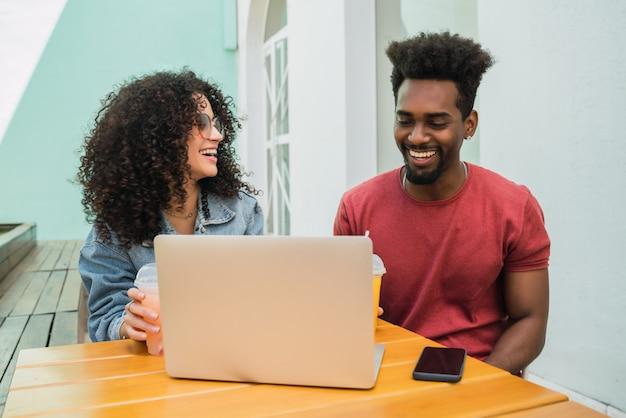 Deux amis afro utilisant un ordinateur portable dans une cafétéria.