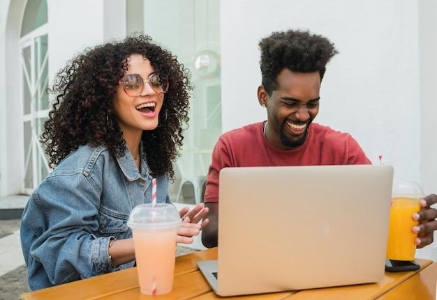Deux amis afro utilisant un ordinateur portable dans une cafétéria