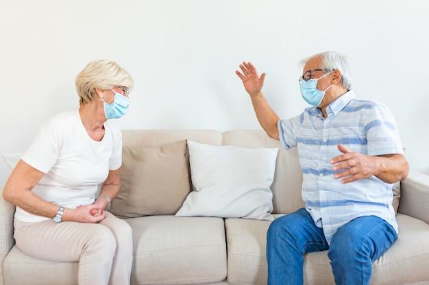 Deux amis âgés assis à distance sociale portant un masque médical