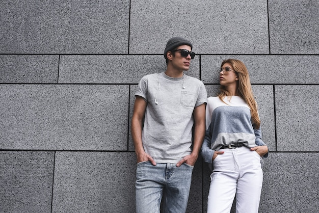 Deux amis appuyés contre un mur et s'ignorant. concept de dépendance à la technologie, mec et femme sur fond de mur gris.