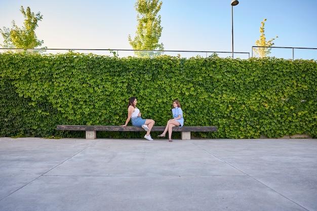 Deux amis assis sur un banc. ils parlent dehors.
