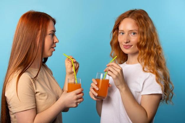 Deux amis aux cheveux roux boivent du jus d'orange sur le mur bleu