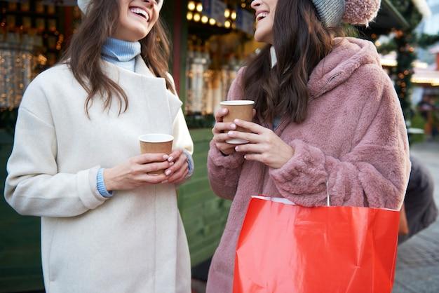 Deux amis bavardant et buvant du vin chaud sur le marché de noël