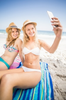 Deux amis en bikini prenant un selfie