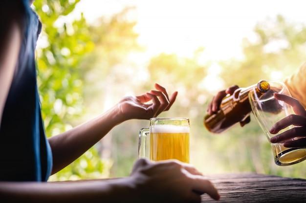 Deux amis buvant de la bière et discutant d'un sujet au balcon en été