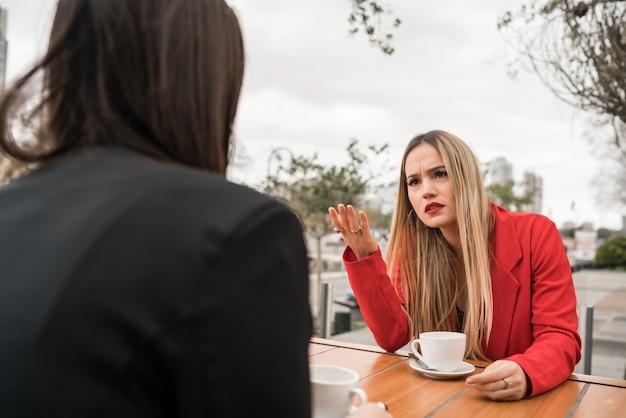 Deux amis en colère discutant assis au café.