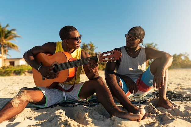 Deux amis cubains s'amusant à la plage avec sa guitare. notion d'amitié.