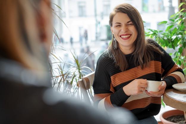 Deux amis dans un café près de la fenêtre