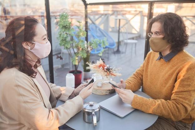 Deux amis dans des masques de protection discutant des applications en ligne sur leurs téléphones mobiles alors qu'ils étaient assis dans un café