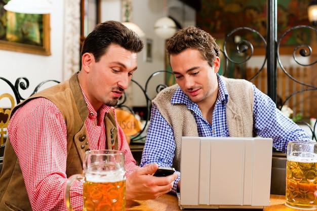 Deux amis dans un pub bavarois avec un ordinateur portable