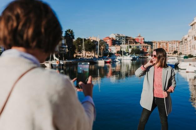 Deux amis dans la rue prenant des photos avec un téléphone portable. fond de port dans une journée ensoleillée. mode de vie à l'extérieur. concept d'amitié