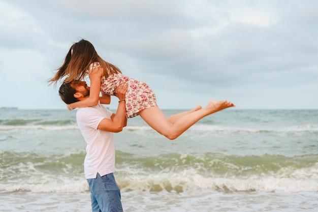 Deux amis avec des droits en jouant sur la plage en sautant.