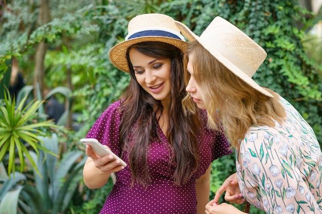 Deux amis enjoués regardent le téléphone, fabriquent des chapeaux de selfie sur un fond vert naturel.