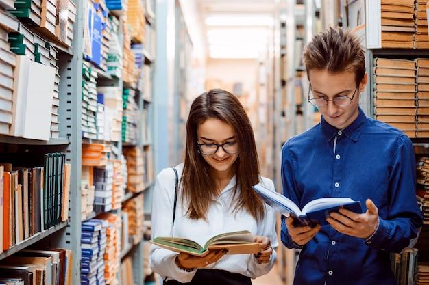 Deux amis étudiants lisant des livres debout dans le long couloir de la bibliothèque