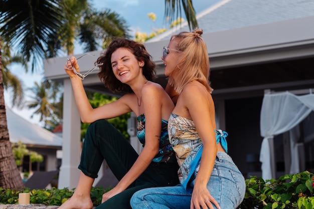 Deux amis femme heureuse avec des lunettes de soleil en vacances dans un pays tropical