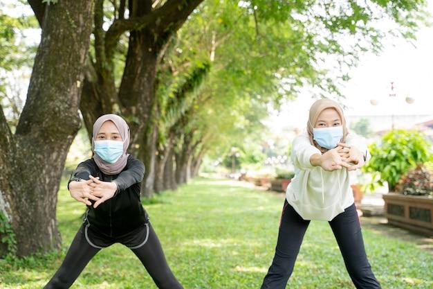 Deux amis de femme musulmane font de l'exercice ensemble et portent un masque