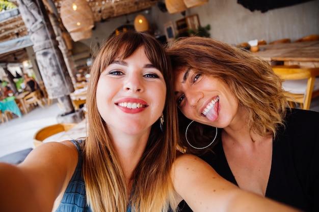 Deux amis de femme de race blanche européenne avec maquillage naturel et cheveux courts prennent selfie au café d'été