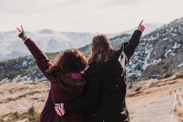 Deux amis femme randonneur réussie profiter de la vue sur le sommet de la montagne au coucher du soleil. femmes heureuses dans la nature