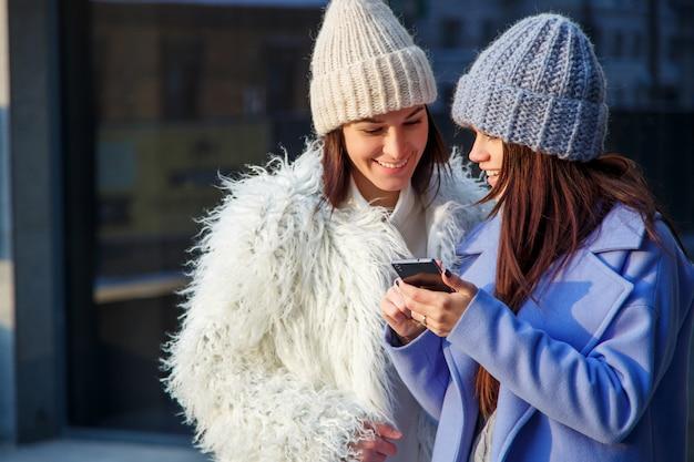 Deux amis femmes partageant des médias sociaux dans un téléphone intelligent à l'extérieur