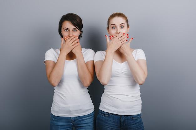 Deux amis femmes posant dans le studio, fermant la bouche avec les bras. concept émotion