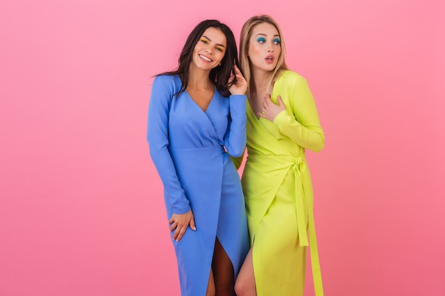Deux amis de femmes séduisantes souriantes élégantes posant sur un mur rose dans des robes colorées élégantes de couleur bleu et jaune, tendance de la mode printanière