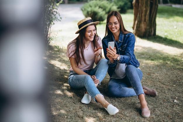 Deux amis filles assis dans un parc
