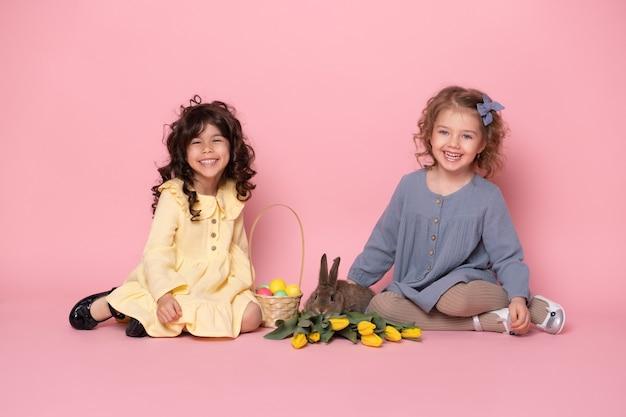 Deux amis filles enfant en belle robe avec lapin, tulipes, panier avec des œufs colorés.