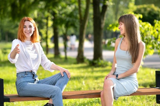 Deux amis filles heureux assis sur un banc à l'extérieur dans le parc d'été bavardant joyeusement s'amusant
