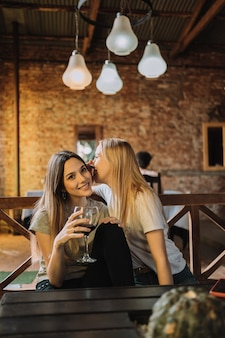 Deux amis heureux célébrant et riant avec un verre de vin rouge dans un restaurant.